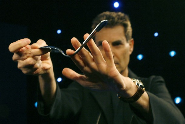 Israeli psychic Uri Geller bends a spoon during a photographers call in Cologne